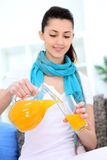 Girl pouring orange juice Stock Photos