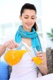 Girl pouring orange juice Stock Photos