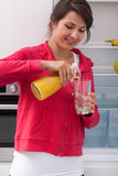 Girl pouring orange juice Royalty Free Stock Photo