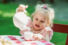 Free Girl Pouring Tea Into The Little Cup Royalty Free Stock Photography - 165603097