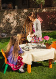 Girl pouring tea to her sister at toy tea party Stock Image