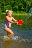 Girl pouring water from a bucket Stock Images