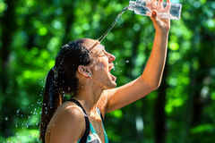 Girl pouring water on face after workout. Close up face shot of female runner pouring water on face after workout. Cold water from bottle splashing on girls royalty free stock photo