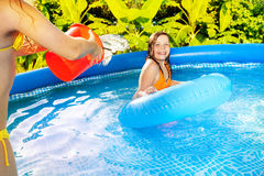 Girl pouring water from red bucket over her friend Royalty Free Stock Photo