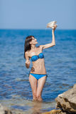 Girl pouring water from shell. Sexy young woman pouring over herself water from the big seashell against the sea Stock Photos