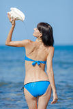 Girl pouring water from shell. Sexy young woman pouring over herself water from the big seashell against the sea Royalty Free Stock Images