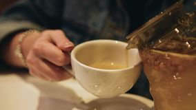 The girl pours a beautiful ginger tea from a teapot into a mug. Close up. Delicious drink stock video footage