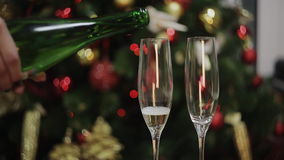 Girl pours champagne in glasses on the background of the Christmas tree. Two Champagne Glasses On Defocused Background Living Room With Christmas Tree stock video footage