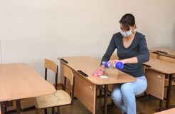 The girl pours cleaning and disinfectant on the desk at the school during the quarantine period