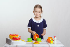Girl pours a cup of cream in children's kitchen Stock Images