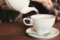 The girl pours a cup of tea Royalty Free Stock Photography