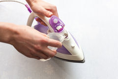 The girl pours distilled water into the tank of flat-iron. Top view during housework. Royalty Free Stock Images