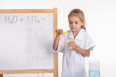 Girl pours liquid from a test tube into flask standing at blackboard Royalty Free Stock Image