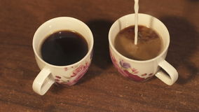 Girl pours the milk into two cups of coffee. Girl pours the milk into two cups of coffee, slow motion stock footage