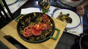 A girl pours paella with seafood and vegetables on a plate - traditional dish of Spanish cuisine.