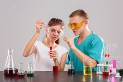 The girl pours a red liquid from a pipette into a flask, the guy shows with the fingers quantity. stock photo