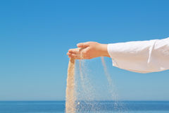 Girl pours sand from his hands. Stock Image