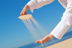 A girl pours sand out of shells on hand. Royalty Free Stock Photography