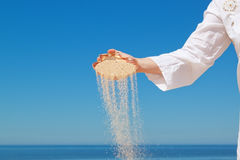 A girl pours sand from the shells. Stock Images