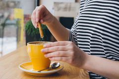Girl pours sugar from a bag into a mug of coffee Royalty Free Stock Photos