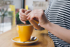 Girl pours sugar from a bag into a mug of coffee Royalty Free Stock Photo