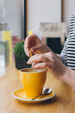 Girl pours sugar from a bag into a mug of coffee Stock Images