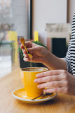 Girl pours sugar from a bag into a mug of coffee Royalty Free Stock Images