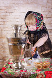 Girl pours tea from a samovar Stock Photo