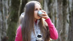 Girl pours tea from a thermos and drink stock video footage