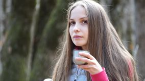 Girl pours tea from a thermos and drink stock footage