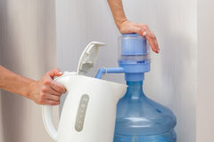 A girl pours water from a cooler in a teapot. Royalty Free Stock Images