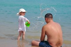 The girl pours water on her father. Splashes of water in the sea. Child and father on vacation. stock images