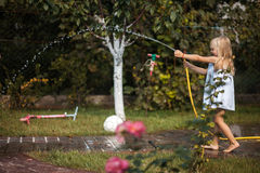 Girl pours water from a hose pot. On a grass royalty free stock photography