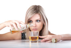 The girl pours whisky from  bottle in  glass Royalty Free Stock Photo