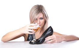 The girl pours whisky from  glass in a shoe Stock Images