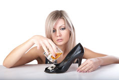 The girl pours whisky from  glass in a shoe Royalty Free Stock Photos