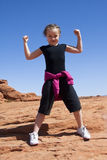 Girl Power. A young girl shows her strength with a proud smile Royalty Free Stock Photography