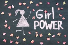 GIRL POWER chalk written message and woman drawing symbol on chalkboard or blackboard. Live pink flowers around. Lettering text s. Ign. Women`s day, feminism or royalty free stock images