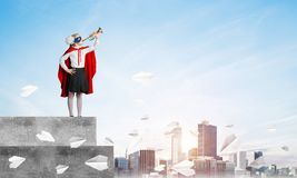 Girl power concept with kid wearing cape and mask and playing trumpet. Mixed media royalty free stock photos