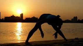 Girl Practice Yoga Pose Wide-Legged Forward Bend. the Action at Sunset on the