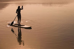 Girl practices stand up paddling Stock Photos
