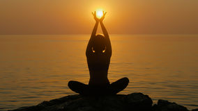 Girl practices yoga near the ocean. Girl holding rising sun in her hands sitting near the ocean Stock Photos
