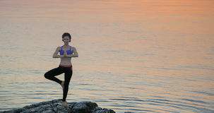 Girl practices yoga near the ocean. During sunrise time Royalty Free Stock Images