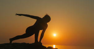 Girl practices yoga near the ocean. During sunrise time Royalty Free Stock Photo