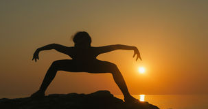 Girl practices yoga near the ocean. During sunrise time Stock Image