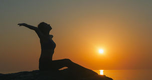 Girl practices yoga near the ocean. During sunrise time Stock Photo