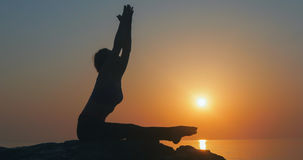 Girl practices yoga near the ocean Royalty Free Stock Image