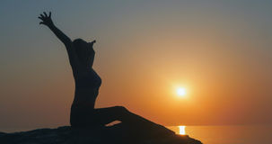 Girl practices yoga near the ocean. During sunrise time Stock Images