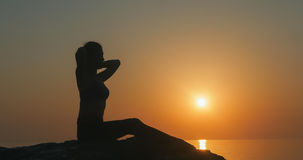 Girl practices yoga near the ocean. During sunrise time Stock Photography