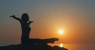 Girl practices yoga near the ocean. During sunrise time Royalty Free Stock Image